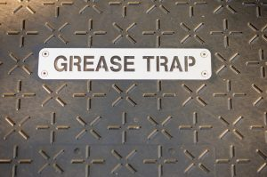 Metal plate with grease trap written on it