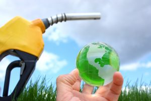 hand holding small earth next to biodiesel fuel pump